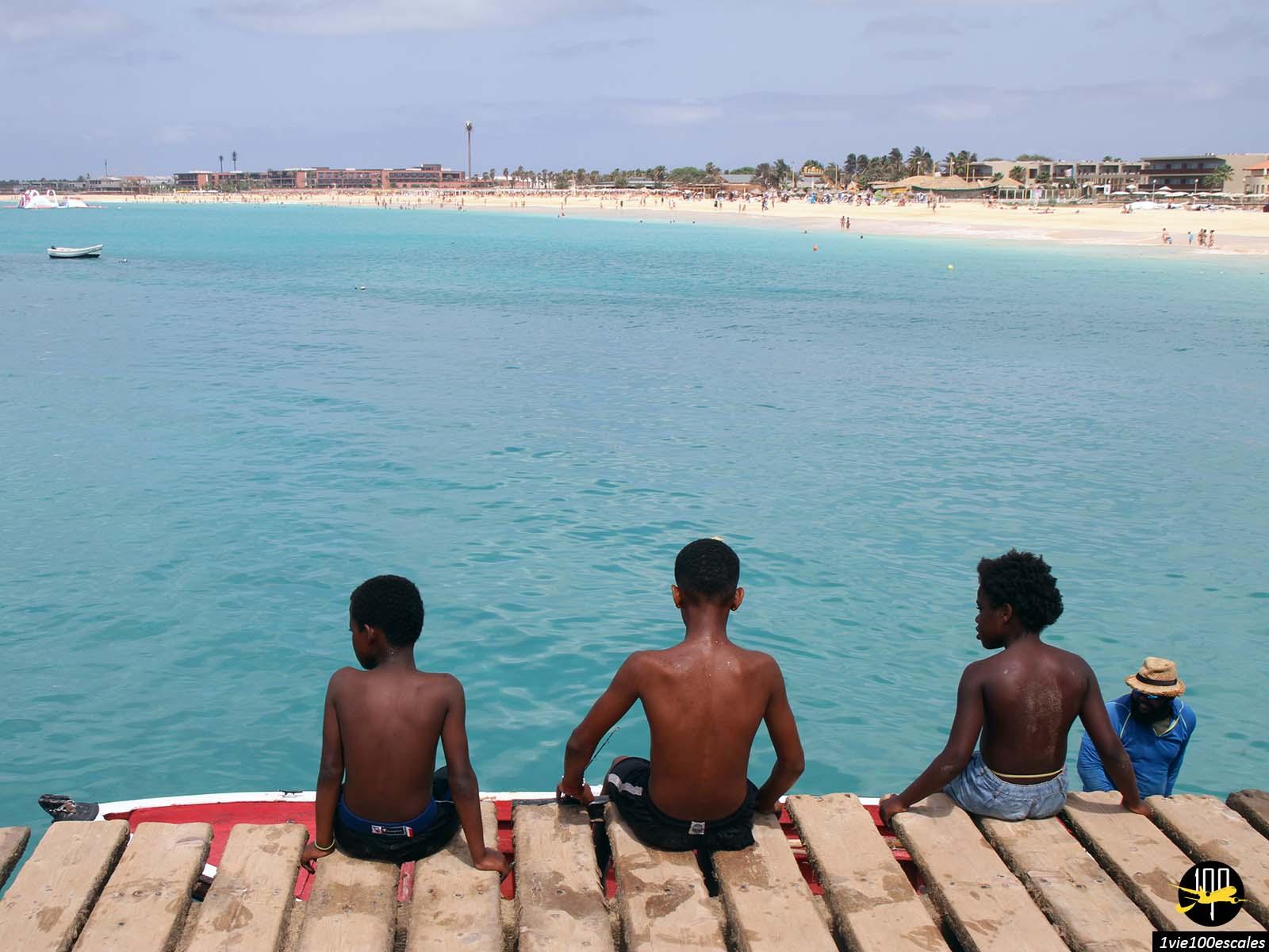 Les enfants jouant sur le ponton à l'arrivée des pêcheurs à Santa Maria sur l'île de Sal