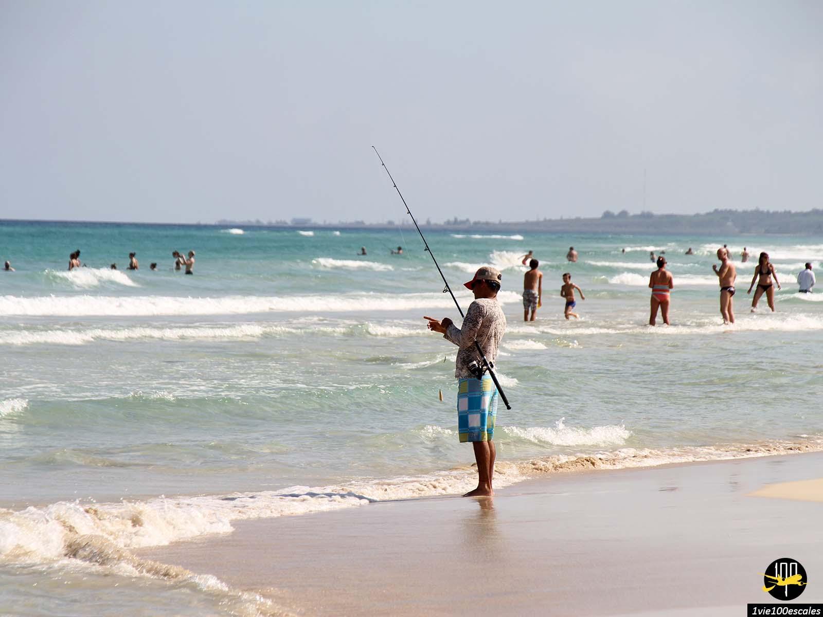 Un pêcheur juste à côté des touristes sur les Playas del Este