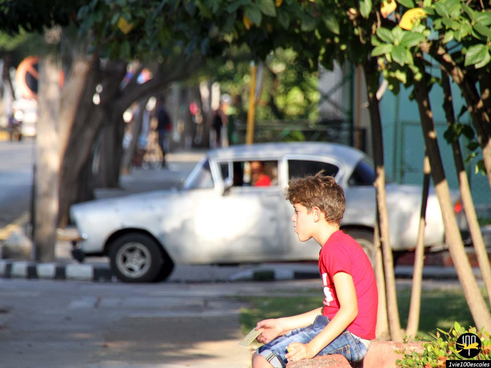 Un enfant et une ancienne voiture dans le village de Varadero